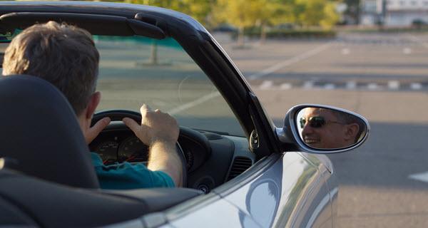 Man Driving A Porsche